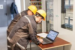 Two maintenance engineers inspect relay protection system with l. Aptop computer. Bay control unit. Medium voltage switchgear Stock Photos