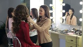 Two make-up artists doing makeup for two models. Group of make-up artists working with models in the beauty salon. Two make-up artists doing makeup for two stock footage