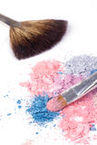 Two make-up brush on crumbled eyeshadows. Closed-up on white Royalty Free Stock Images