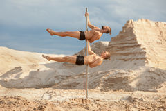 Two male acrobats are dancing on a pylon. Two men of acrobats dance on a pylon, in the background a desert and sand royalty free stock photography