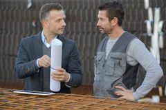 Two male architects discussing blueprint outdoors royalty free stock photos