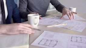 Two male architects are discussing the building blueprints, close up. Professionals are sitting at the wooden table with papes, coffee cups and notebook on stock video footage