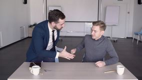 Two male architects are finishing their co-working in the conference room. Professional with beard and in blue suit with tie collects paper blueprints from the stock video