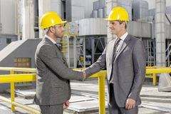 Two male architects shaking hands at construction site Royalty Free Stock Photo