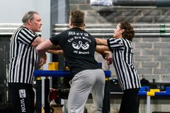 Two male arm wrestlers and referees in a tough fight. STOCKHOLM, SWEDEN - JANUARY 13, 2018: Two referees adjusting the hands on a Swedish male armwrestler at Stock Images