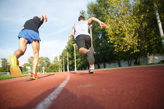Two male athletes competing on running track Stock Photos