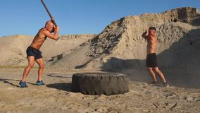 Two male athletes training together hit the wheel with a hammer at sunset in the mountains on the sand. Endurance. Training stock footage