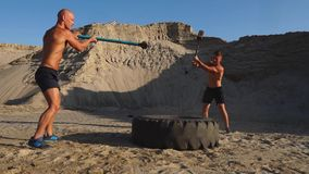 Two male athletes training together hit the wheel with a hammer at sunset in the mountains on the sand. Endurance. Training stock video footage