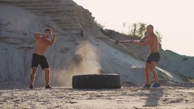 Two male athletes training together hit the wheel with a hammer at sunset in the mountains on the sand. Endurance. Training stock video