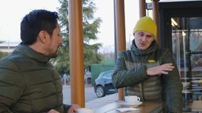 Two male athletes in warm bubble jackets talk after training in the outdoor area of the cafe in the evening. The guy. With yellow knit cap tells something about stock video