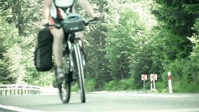 Two male bicycle tourists climbing up the mountain asphalt road. Unidentified male bicycle tourists climbing up the mountain forest road stock video