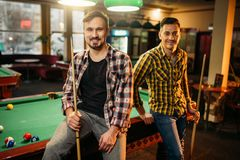 Two male billiard players with cues poses. At the table with colorful balls, poolroom. Men plays american pool game in sport bar royalty free stock photos