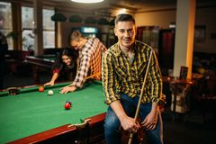 Two male billiard players with cues poses. At the table with colorful balls, poolroom. Men plays american pool game in the sport bar royalty free stock photo