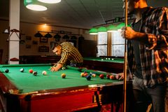 Two male billiard players with cues poses. At the table with colorful balls, poolroom. Men plays american pool game in the sport bar stock images