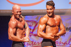 Two male bodybuilders show their best at championship on stage Stock Photo