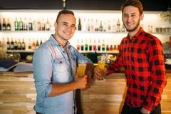 Two bowlers drinks juice at the bowling club bar. Two male bowlers drinks fresh juice at the bowling club bar counter. Players relax after competition. Active stock photography