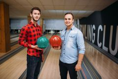 Two male bowlers poses on lane with balls on hands. Bowling alley players before competition. Classical tenpin game in club, active leisure royalty free stock image