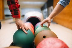 Two male bowlers takes balls from feeder. Bowling alley players prepares to makes a throw. Classical tenpin game in club, active leisure stock photo