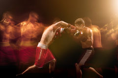 The two male boxers boxing in a dark studio. The two male athlete boxers punching with dramatic edgy lighting in a dark studio. Image made with stroboscope Royalty Free Stock Photos