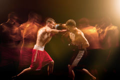 The two male boxers boxing in a dark studio. The two male athlete boxers punching with dramatic edgy lighting in a dark studio. Image made with stroboscope Stock Image