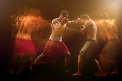 The two male boxers boxing in a dark studio. The two male athlete boxers punching with dramatic edgy lighting in a dark studio. Image made with stroboscope Royalty Free Stock Photography
