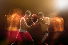 The two male boxers boxing in a dark studio. The two male athlete boxers punching with dramatic edgy lighting in a dark studio. Image made with stroboscope Royalty Free Stock Photo