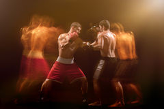 The two male boxers boxing in a dark studio. The two male athlete boxers punching with dramatic edgy lighting in a dark studio. Image made with stroboscope Stock Photos