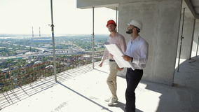 Two male builders walking through the building under construction stock video footage