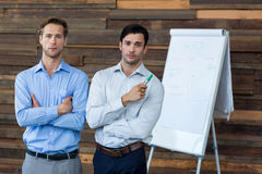 Two male business executives in a meeting standing in front of a flip chart Stock Image