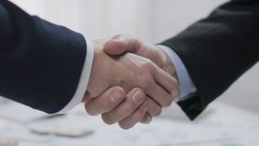 Two male business partners shaking hands, profitable agreement, co-operation. Stock footage stock footage