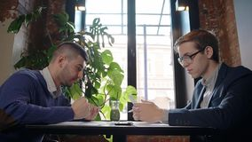 Two male businessmen working together on printed financial report in the cafe. Concept of: businessman working, business people, working together, business stock video