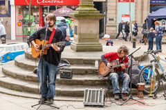 Two Male busker playing guitars and singing at the Lymelight Fes Stock Photos
