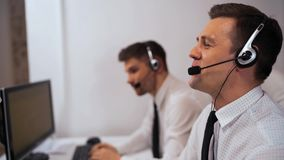 Two male call centre support specialist talking with customers by headsets.
