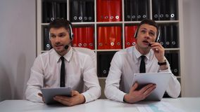Two male in call-centre talking with customers by headsets. Two call-centre technical support specialist businessmen talking with customers by headsets hands stock footage