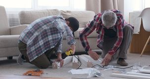 Two carpenters assembling furniture at home stock video