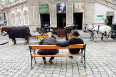 Two male coachmen sitting on the bench Royalty Free Stock Photos