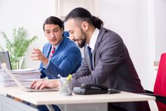 The two male colleagues in the office. Two male colleagues in the office royalty free stock image