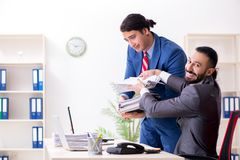 The two male colleagues in the office stock image
