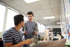 Two Male College Students Building Machine In Science Robotics Or Engineering Class stock images