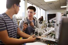 Two Male College Students Building Machine In Science Robotics Or Engineering Class stock image