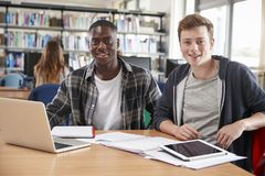 Two Male College Students Collaborating On Project In Library Stock Photos