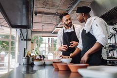 Chefs talking while cooking food in commercial kitchen. Two male cooks preparing food on restaurant kitchen. Chefs talking while cooking food in commercial Royalty Free Stock Images
