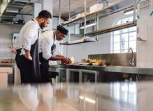 Chefs cooking food in commercial kitchen. Two male cooks preparing food on restaurant kitchen counter. Chefs cooking food in commercial kitchen Royalty Free Stock Images