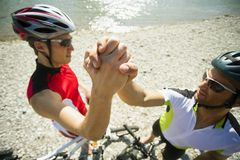Two male cyclists shake hands. Royalty Free Stock Photo