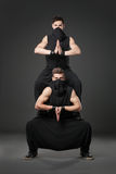 Two male dancers posing in ninja costumes on dark gray backgroun Stock Photo