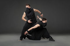 Two male dancers posing in ninja costumes on dark gray backgroun Stock Image