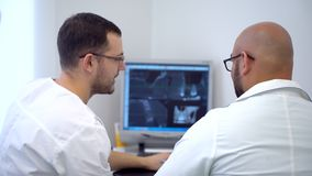 Dentists having discussion on x-ray at dental clinic. Two male dentists have a discussion with x-ray prints at modern dental clinic. 4 k healthcare, medical and stock footage