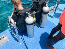 Two male divers in black diving waterproof suits with shiny metal aluminum canisters are preparing to dive from the boat to the bl. Ue sea water on vacation royalty free stock photo
