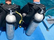 Two male divers in black diving waterproof suits with shiny metal aluminum canisters are preparing to dive from the boat to the bl. Ue sea water on vacation royalty free stock photography