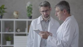 Two male doctors checking information on the tablet, discussing. Concept of medicine, technology, health care and people